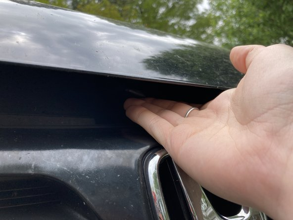 Find the hood-release latch underneath the hood, just above the Honda logo on the grill of your vehicle.