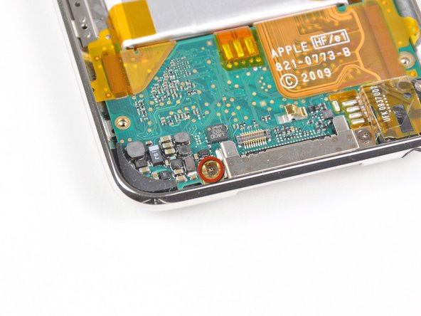 Remove the single Phillips screw securing the gold pressure contact to the logic board.