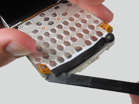 Insert the flat edge of the spudger to the space under the keypad and slide it along the bottom to lift the keypad out of its place. The keypad should be stuck to the surface very tightly.