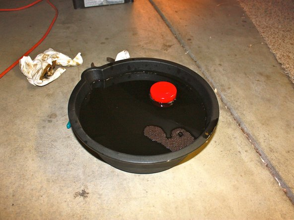 Drain the remaining oil in the filter by inverting it over the drip pan.