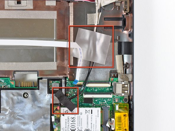 If present, remove the pieces of tape securing the Wi-Fi antenna cables to the upper case.