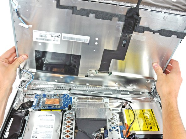 Rotate the display until it is nearly perpendicular to the rear case and lift it up to peel it off the EMI shield stuck to its top edge.