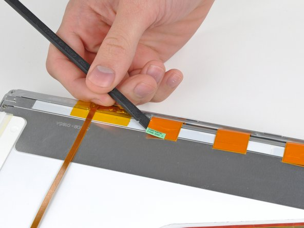 Use the flat end of a spudger to carefully peel off the three antenna straps stuck to the lower edge of the LCD.