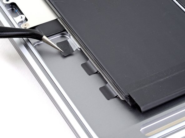 The MacBook's battery cells are attached to a metal tray as a complete assembly, which is adhered to the case with a total of six stretch-release adhesive strips.