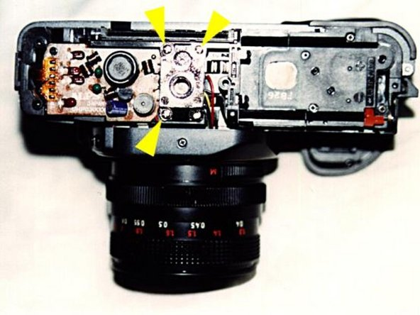 After you have removed the bottom cover, you still have to reach the wire contacts that are hidden by the tripod mount. The tripod mount can be easily removed by unscrewing the three crosshead screws using the larger screwdriver.