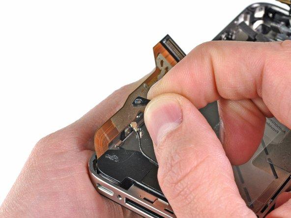 Enlevez le petit dispositif en plastique sous la vis la plus près de la nappe du connecteur de dock.