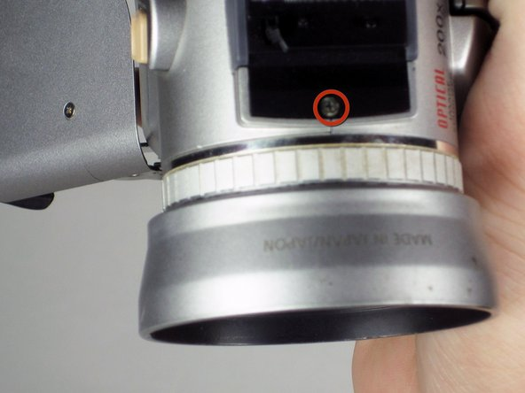 Reorient the camera with the top facing you.  The side with the LCD screen should be on the right and the other side panel should be on the right.