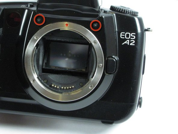 Remove the two 6.4mm screws above the lens aperture using a phillips #00 screw driver.