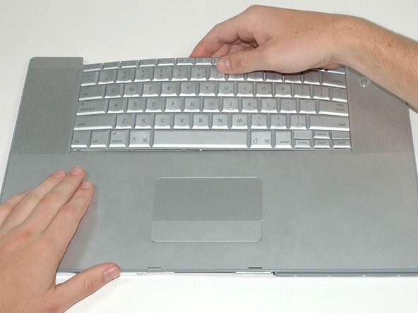 Maintaining your hold on the keyboard, lay the casing flat and gently bow the keyboard until the two tabs on either side of the keyboard come free.