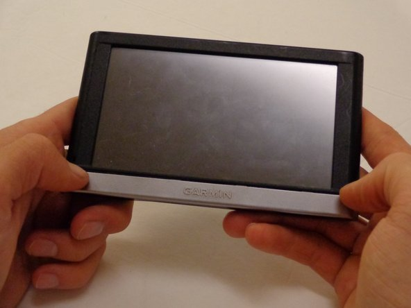Grip the device with your hands. Using your thumbs pull the nameplate towards yourself and off the device.