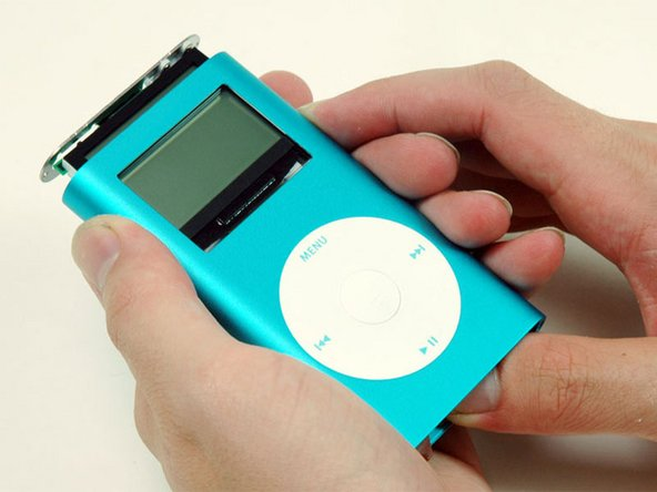 Carefully slide the iPod out of its casing by pushing on the logic board near the bottom edge of the click wheel.