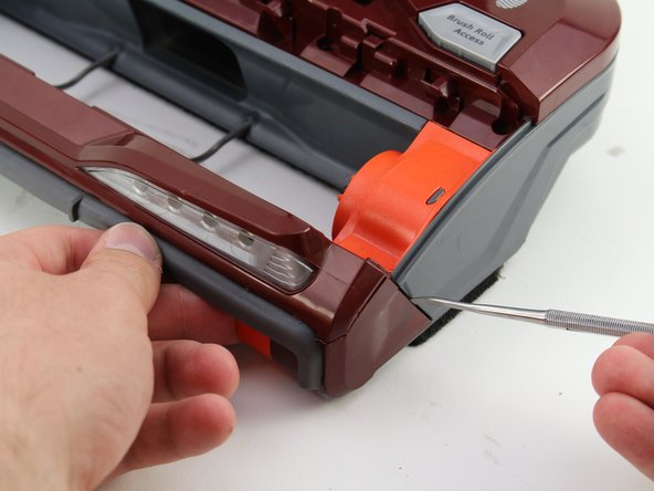 Use the spudger tool to pry off the red plastic corner cap.