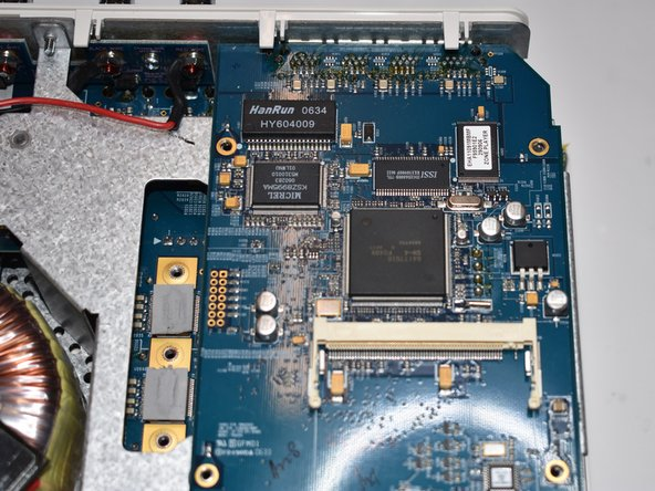 Hebe die Netzwerkkarte schräg an und ziehe es mitsamt der Ethernet-Ports in Richtung Vorderseite ein Stück aus seiner Fixierung auf der Rückseite.