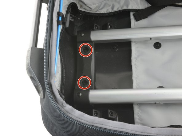 Remove the two Phillips #1 screws from the retaining bracket at the bottom of the bag.