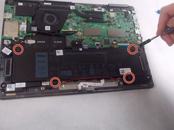 Use a Phillips screwdriver to remove the four screws holding the battery in place.