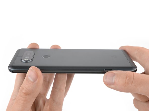 Press the button on the lower right side of the LG V20 to open the clamp that holds the back cover on the back side of the phone.
