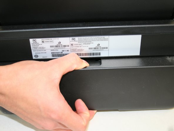 Hold the button down with the flat end away from the printer. When you hear a click, the duplex unit can be removed from the printer.