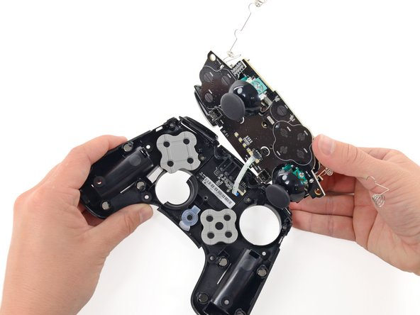 """Inside the controller we find a stack of two circuit boards—the top hosts contacts for the directional pad and """"O, U, Y, A"""" buttons, while the lower is home to the two analog joysticks."""
