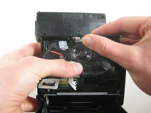 Carefully remove the damaged lens from the interior of the camera.