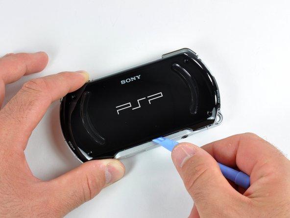 プラスチックの開口ツールをバックカバーの周辺に差し込んでスライドして、四方全てに留められた接着剤を緩めます。