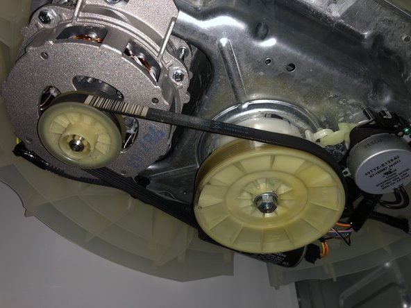 Following removal of the cover you will see the drive belt roped around two  cogs.