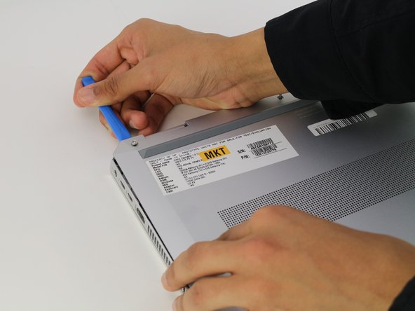 Remove the base by inserting the plastic opening tool into the slit between the two portions of the case and gently prying the metal cover away from the body of the device.