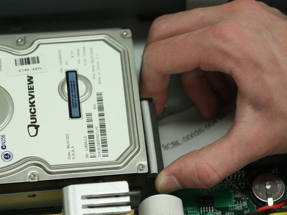 Grab the hard drive data cable from both sides of the connector and unplug it from the hard drive.