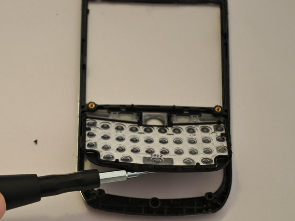 Gently pry the side release tabs to lift the flexing keypad from the frame.