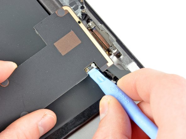 Use the edge of a plastic opening tool to pry the Wi-Fi antenna connector up from its socket on the logic board.