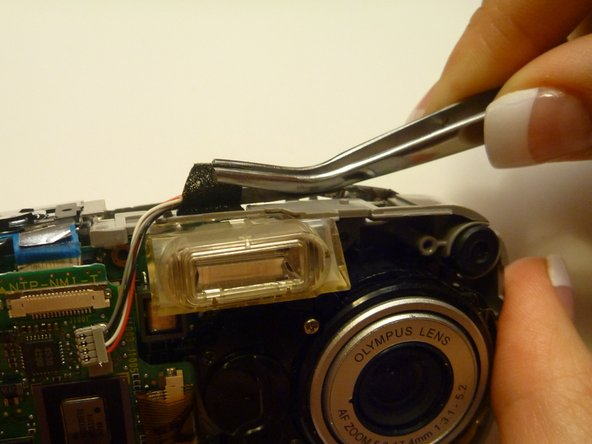 Locate the tape securing the wiring with the gray end piece located on top of the camera.