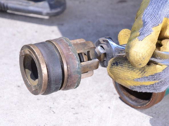 Insert a wrench into the slots located at the bottom of the traveling valve.