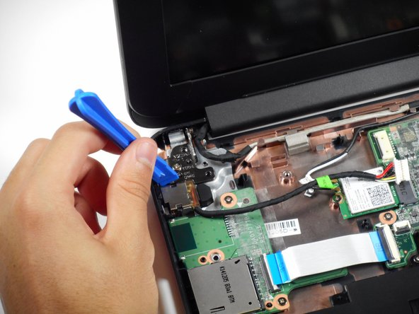 Locate the two brown clips that secure the charging port to the motherboard from both edges.