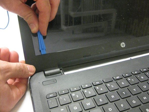 With the screen facing you, use the plastic opening tool to remove the liner around the screen