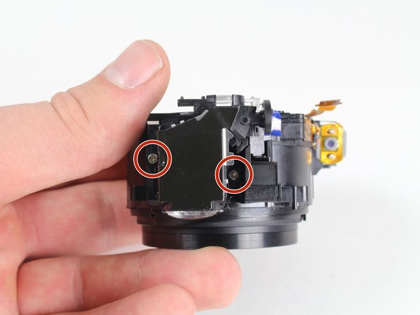 Remove the two 2.8 mm screws on the top of the lens assembly near the viewfinder using a Phillips #00 screwdriver.