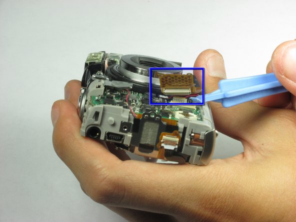 Use a spudger or a flathead screwdriver to remove the camera lens cable located in the front of the camera.