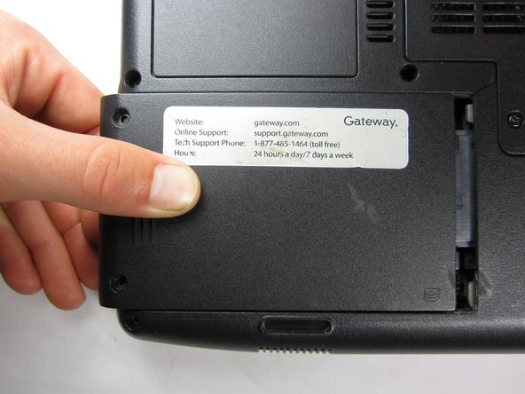 Press thumb down firmly on the hard drive and pull outwards to the side.