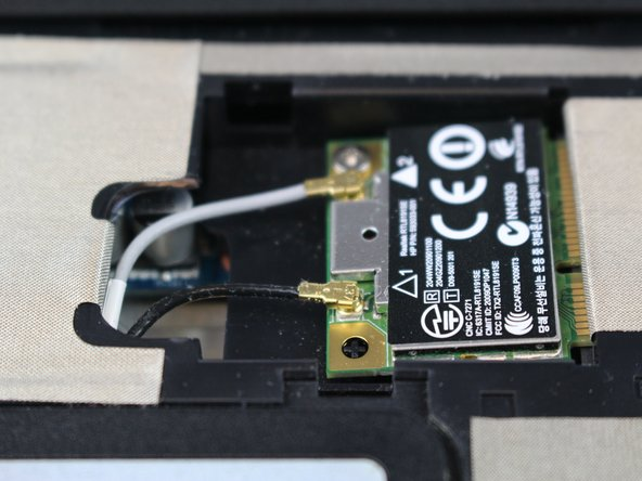 Gently pull the black and white cables to disconnect them from the Wi-Fi card.
