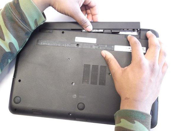 Then take and slide the other switch to the other end of its track which will pop out the battery.