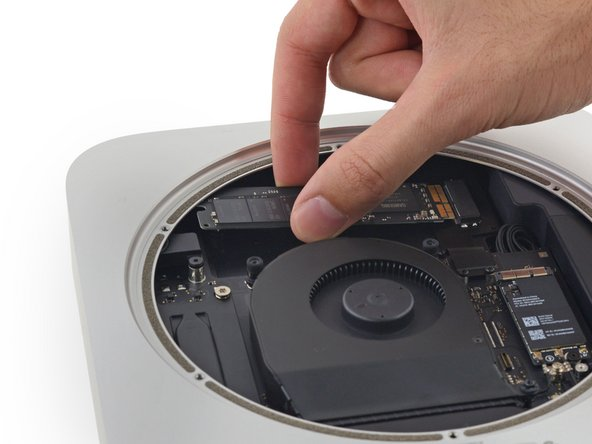 Carefully lift the SSD out of the case without scratching or touching the gold contacts.