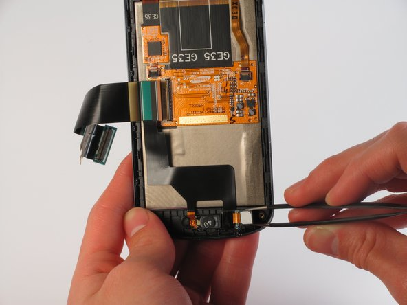 Use tweezers to loosen the front-facing camera from the plastic casing.