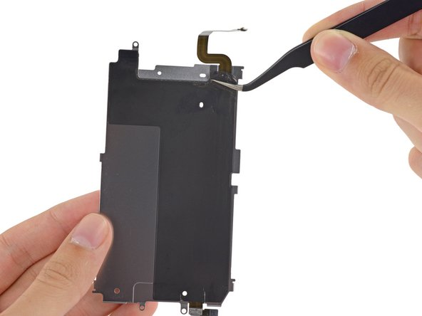 Peel the black backing tape away from the home button cable.