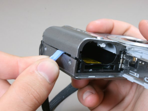 Slide the battery door open and slightly open the side of the case with a plastic opening tool.