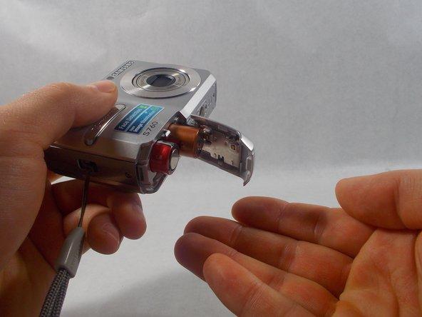 拿起相机,轻轻地让电池从相机中滑出来。