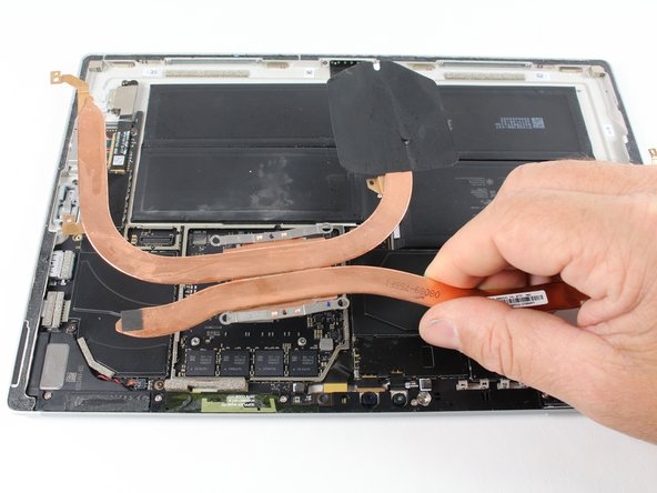 Remove the heat sink from the device by grabbing one of the copper bars with your fingers and lifting straight up.