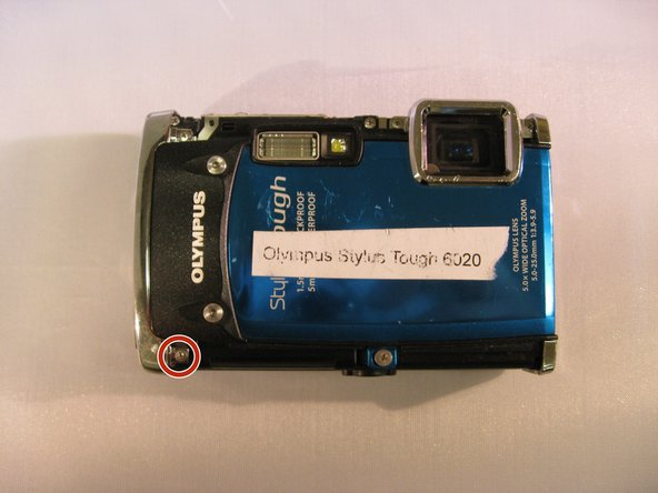 """Using a Phillips 00 screwdriver, unscrew the 3.9mm screw located next to the black """"Olympus"""" face plate."""