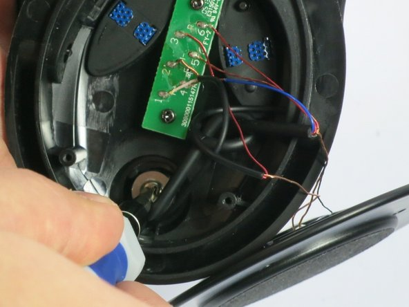 Remove the 9/32 inch screw with a Philips 2 screwdriver to gain access to microphone.