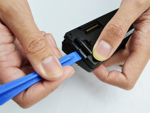 Use the plastic opening tool to pry it open.