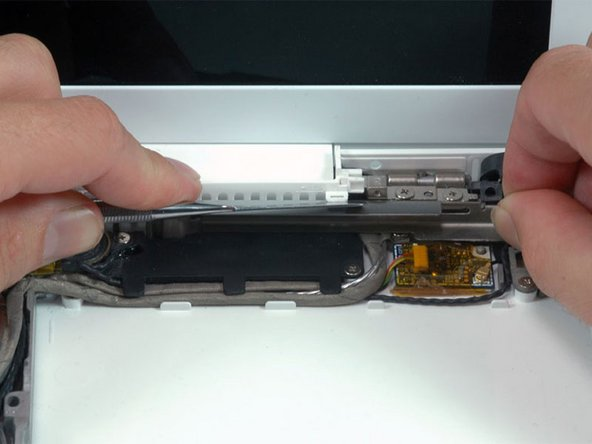 Using a spudger, gently pry up the white plastic slot and slide the metal c-channel to the right and away from the display.