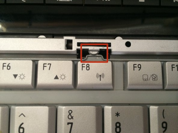 Find the latch above the F8 key that overlaps the keyboard.