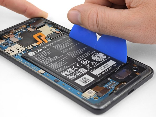 Insert a couple of opening picks or a plastic card along the right edge of the battery.